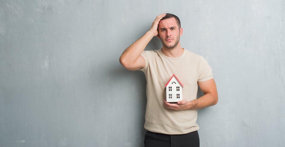 Mann mit Modellhaus in der Hand fasst sich an Kopf