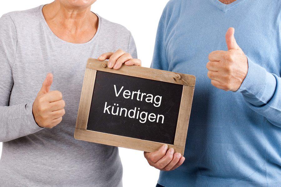 Ehepaar hält Schild mit Aufschrift Vertrag kündigen