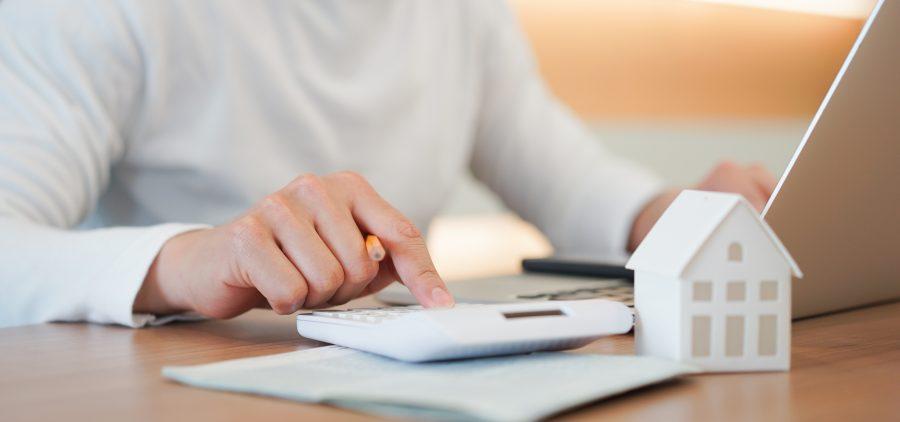 Frau am PC mit Modellhaus und Taschenrechner